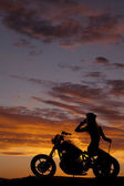 Silhouette of woman motorcycle sit backwards hand — Stock Photo