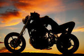 Woman lay on back of motorcycle silhouette — Stock Photo