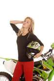 Woman red pants green motorcycle holding helmet — Stock Photo