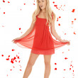 Woman red dress hold skirt rose petals. — Stock Photo