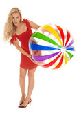Woman red dress beach ball lean over — Stock Photo