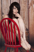 Woman nose ring red chair backwards barefoot — Stock Photo