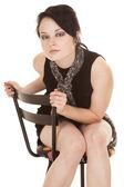 Woman black dress scarf sit lean forward — Stock Photo