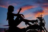 Silhouette woman motorcycle heels up hand knee — Stock Photo