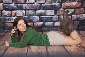 Green shirt scarf rock wall phone lay stomach look back — Stock Photo