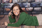 Green shirt scarf rock wall phone lay stomach smile — Stock Photo