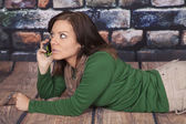 Green shirt scarf rock wall phone lay stomach serious — Stock Photo