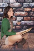 Green shirt sit rock wall book look — Stock Photo