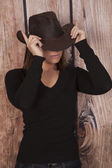 Woman cowgirl wooden wall hands on hat — Stock Photo