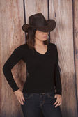 Woman cowgirl wooden wall eyes hid — Stock Photo