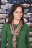 Woman scarf green shirt brick wall serious — Stock Photo