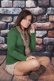Woman scarf green shirt phone rocks talk lips — Stock Photo