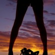 Silhouette woman legs motorcycle under — Stock Photo #35089175