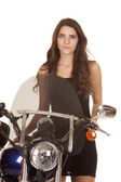 Woman in black stand by motorcycle serious — Stok fotoğraf