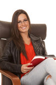 Woman red shirt black jacket sit read smile — Stok fotoğraf