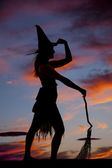 Silhouette woman witch broom hold hat — Stock Photo