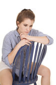 Woman blue striped shirt sit backwards look down — Stock Photo