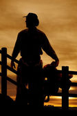Silhouette cowboy saddle in front of fence — Stock Photo