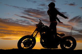Silhouette woman motorcycle stand hands back — Stock Photo