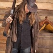 Cowboy duster long hair rifle over shoulder by wall — Stock Photo
