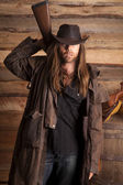 Cowboy duster long hair rifle behind back — Stock Photo