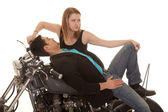 Man lay back on motorcycle woman look back — Stock Photo