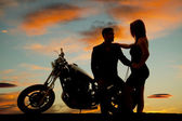 Silhouette of woman by man on motorcycle — Stock Photo