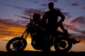 Woman lay back on motorcycle man stand silhouette — Stock Photo
