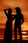 Cowboy couple stand silhouette her hand on head — Stock Photo