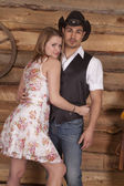 Cowboy with woman arms around him — Stock Photo