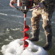 Man in camo drilling hole in ice body — Stock Photo