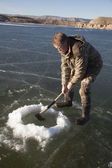 Man in camo chopping hold in ice with axe down — Stockfoto