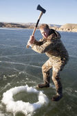 Man in camo chopping hole in ice with axe swing — Stock Photo