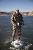 Man in camo drilling hole in ice look down — Stock fotografie