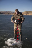Man in camo drilling hold in ice with auger — Stock Photo