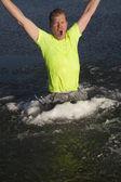 Man in ice hole green shirt jump — Stock Photo