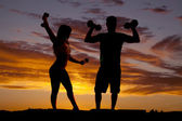 Silhouette couple with weights flex — Stock Photo