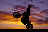 Silhouette woman motorcycle ride wheelie — Stock Photo