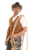 Cowboy in vest with rope on shoulder — Stock Photo