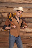 Man with a saddle on his back cowboy hat — Stock Photo