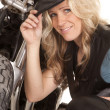Stock Photo: Womleather hat kneel by motorcycle smile