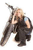 Woman in leather kneel by motorcycle serious — Stock Photo