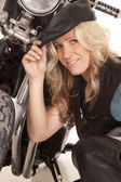 Woman leather hat kneel by motorcycle smile — Stock Photo