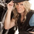 Stock Photo: Womleather hat kneel by motorcycle funny face