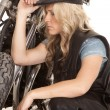 Stock Photo: Womleather hat kneel by motorcycle look side