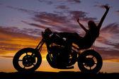 Mujer de silueta en los brazos de una motocicleta en el aire — Foto de Stock