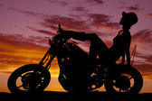 Silhouette of woman sit back on motorcycle hat on — Stockfoto
