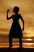 Silhouette woman boots dress hand up — Stock fotografie