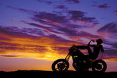 Silhouette woman on motorcycle finger on chin — Stock Photo
