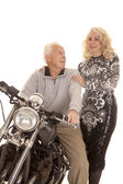 Elderly couple him on motorcycle her stand — Stock Photo